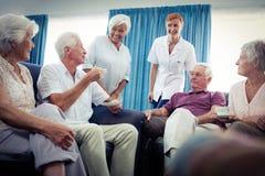 Groupe d'aînés agissant l'un sur l'autre avec l'infirmière Photos libres de droits