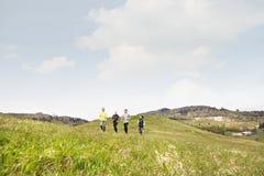 Groupe d'aînés courant dehors sur les collines vertes Images libres de droits