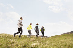 Groupe d'aînés courant dehors sur les collines vertes Photo stock