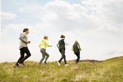 Groupe d'aînés courant dehors sur les collines vertes Image libre de droits