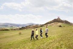Groupe d'aînés courant dehors sur les collines vertes Photos libres de droits