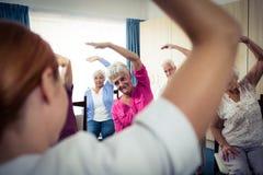 Groupe d'aînés faisant des exercices avec l'infirmière Photographie stock