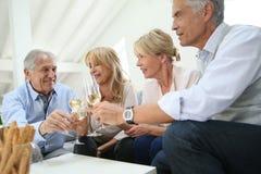 Groupe d'aînés faisant le pain grillé avec le champagne Image stock