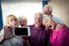 Groupe d'aînés faisant un selfie avec un smartphone et des visages drôles Image libre de droits