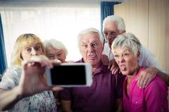 Groupe d'aînés faisant un selfie avec un smartphone et des visages drôles Photo libre de droits