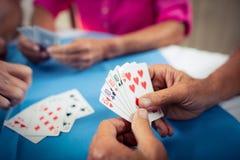 Groupe d'aînés jouant des cartes Photos stock