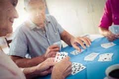 Groupe d'aînés jouant des cartes Images stock