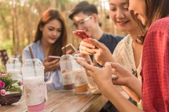 Groupe d'adolescent ajoutant le media social de jeu d'ami avec le smartphon Photo stock