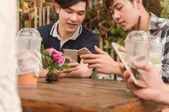 Groupe d'adolescent ajoutant le media social de jeu d'ami avec le smartphon Images stock