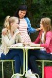 Groupe d'adolescentes s'asseyant au café extérieur Photographie stock