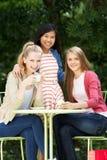 Groupe d'adolescentes s'asseyant au café extérieur Images libres de droits