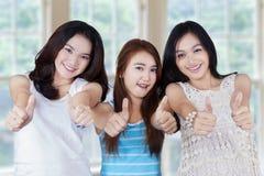 Groupe d'adolescentes tenant un conseil vide Image stock