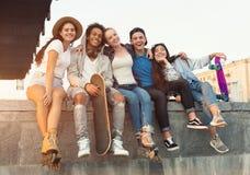 Groupe d'adolescents actifs riant ensemble, soirée de ville image stock