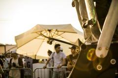 Groupe d'adolescents avec leurs planches à roulettes sur la rampe participant en concurrence pendant un coucher du soleil photographie stock