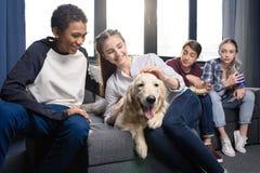 Groupe d'adolescents ayant l'amusement ainsi que le chien de golden retriever à l'intérieur Photo libre de droits