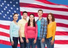 Groupe d'adolescents de sourire au-dessus de drapeau américain Images stock