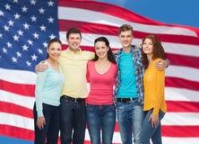 Groupe d'adolescents de sourire au-dessus de drapeau américain Photographie stock