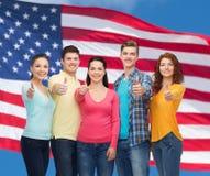 Groupe d'adolescents de sourire au-dessus de drapeau américain Photographie stock libre de droits