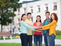 Groupe d'adolescents de sourire au-dessus de fond de campus Photographie stock