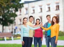 Groupe d'adolescents de sourire au-dessus de fond de campus Image stock