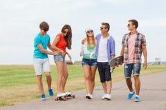 Groupe d'adolescents de sourire avec des planches à roulettes Photographie stock libre de droits