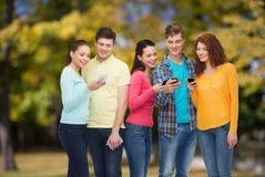 Groupe d'adolescents de sourire avec des smartphones Photographie stock