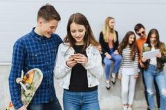 Groupe d'adolescents de sourire avec la planche à roulettes de smartphone photo stock