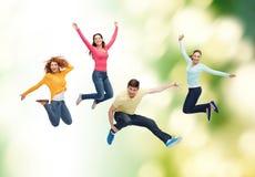 Groupe d'adolescents de sourire sautant en air Photographie stock libre de droits