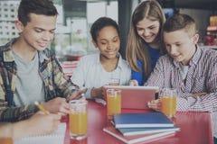 Groupe d'adolescents faisant le travail avec la Tablette Image libre de droits