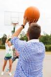 Groupe d'adolescents heureux jouant le basket-ball Photo stock
