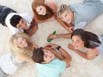 Groupe d'adolescents jouant la rotation la bouteille Photographie stock