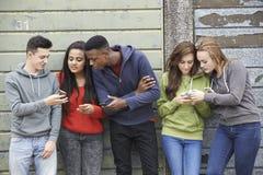 Groupe d'adolescents partageant le message textuel aux téléphones portables Images stock