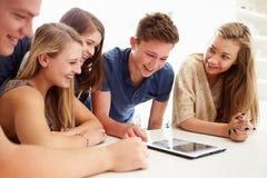 Groupe d'adolescents recueillis autour de la Tablette de Digital ensemble Photographie stock