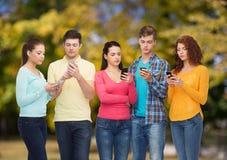 Groupe d'adolescents sérieux avec des smartphones Photo libre de droits