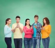 Groupe d'adolescents sérieux avec des smartphones Image libre de droits