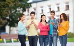 Groupe d'adolescents sérieux avec des smartphones Photo stock