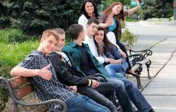Groupe d'adolescents s'asseyant à l'extérieur Images stock