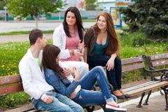 Groupe d'adolescents s'asseyant à l'extérieur Photo stock