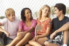 Groupe d'adolescents s'asseyant dans la cour de jeu Images libres de droits