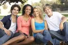 Groupe d'adolescents s'asseyant dans la cour de jeu Photo stock