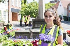 Groupe d'adolescents utiles plantant et rangeant la fleur communale images libres de droits