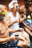 Groupe d'adultes supérieurs divers s'asseyant par la piscine appréciant le résumé Image libre de droits