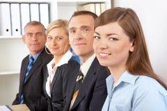 Groupe d'affaires s'asseyant dans la ligne image stock