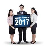 Groupe d'affaires tenant le numéro 2017 sur le panneau d'affichage Image stock
