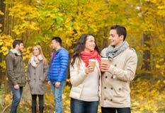 Groupe d'ami de sourire avec des tasses de café en parc Images stock