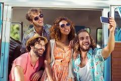 Groupe d'ami heureux prenant un selfie dans campervan Image libre de droits