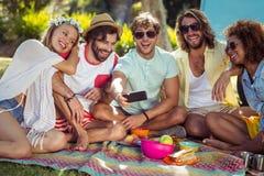 Groupe d'ami heureux prenant un selfie en parc Image libre de droits