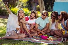 Groupe d'ami heureux prenant un selfie en parc Photos libres de droits
