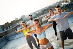 Groupe d'amies convenables heureuses des jeunes dans les v?tements de sport faisant des exercices Sport dehors images stock