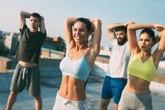 Groupe d'amies convenables heureuses des jeunes dans les v?tements de sport faisant des exercices Sport dehors photo stock